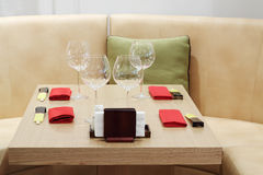 Empty glasses on small wooden table, red napkins Royalty Free Stock Photography