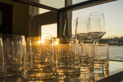 Empty glasses of whiskey and wine at sunset on indoor table with river view windows stock images