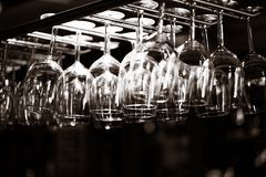 Empty glasses for wine above a bar rack Royalty Free Stock Image