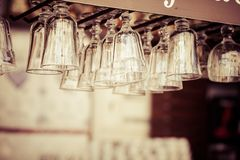 Empty glasses for wine above a bar rack Royalty Free Stock Images