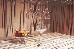 Empty glasses for wine above a bar rack. dried fruits Royalty Free Stock Image