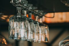 Empty glasses for wine above a bar rack in vintage. Tone Stock Image