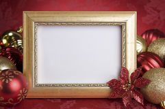 Empty Gold Frame with Christmas Ornaments on a red Background Royalty Free Stock Image