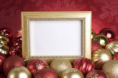 Empty Gold Frame with Christmas Ornaments on a Red Background Stock Image