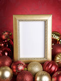 Empty Gold Frame with Christmas Ornaments on a Red Background Stock Images