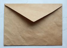 an empty golden envelope on the table, kraft paper, copy space royalty free stock image