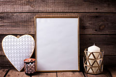 Empty golden frame, decorative heart  and  candles  on  aged woo Royalty Free Stock Photo