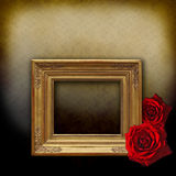 Empty golden frame with red roses. A baroque golden frame with two red roses on a vintage background royalty free stock image