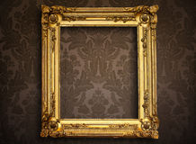 Empty golden frame on vintage wallpaper Royalty Free Stock Images