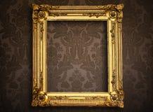 Empty golden frame on vintage wallpaper Royalty Free Stock Images