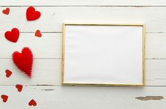 Empty golden frame on wooden background with red hearts. Top view. Flat lay. Valentines day Royalty Free Stock Photo