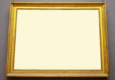 Empty golden picture frame hanging on wall Stock Image