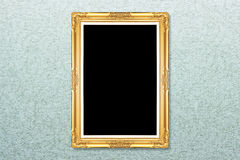 Empty golden vintage frame on wallpaper Stock Images