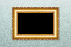 Empty golden vintage frame on wallpaper Stock Photos