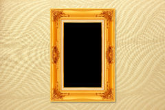 Empty golden vintage frame on wallpaper Royalty Free Stock Photography