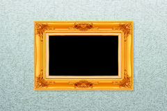 Empty golden vintage frame on wallpaper Stock Photo
