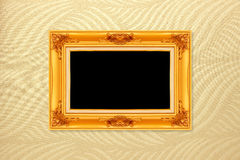 Empty golden vintage frame on wallpaper background Stock Photography