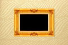 Empty golden vintage frame on wallpaper background Stock Photography