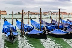 Empty gondolas docked between wooden mooring poles covered in tarpaulin in rainy November season in Venice, Italy stock images