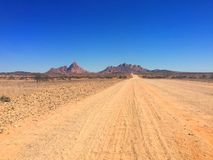 Empty gravel road to mountain with blue sky royalty free stock images