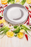 Empty gray plate with fresh herbs and spices on white wooden background Stock Image