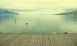 Empty gray wooden pier on Lake Geneva Stock Photos