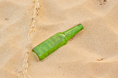 Empty green beer bottle on beach Royalty Free Stock Images