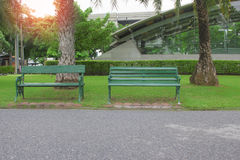 Empty green bench at side of pathway in  Park, Stock Image