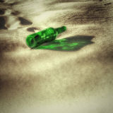 Empty green bottle on the sand Royalty Free Stock Image