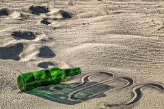 Empty green bottle on the sand Stock Image