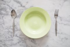 Empty Green Dish with Stainless Forks and Spoon, on White Marble Stone Table Background. S Stock Photos