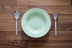 Empty Green Dish with Stainless Forks and Spoon, on Wood Texture Background Stock Photos