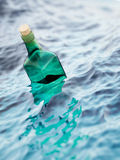 Empty green glass bottle in the sea Royalty Free Stock Photo