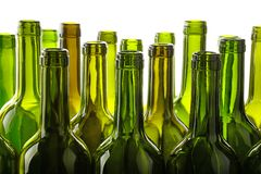 Empty green glass wine bottles isolated on white. Close up group of many empty washed green glass wine bottles in a row isolated on white background, low angle Royalty Free Stock Photography