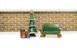Empty green long bench near Christmas tree and gifts. In front of brick wall Royalty Free Stock Photos