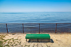 Empty green wooden bench on the sea coast Royalty Free Stock Photo