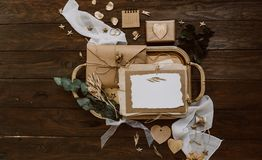 Empty greeting card with kraft envelope and gold decorations on wooden background. Wedding concept. Top view, flat lay stock photography