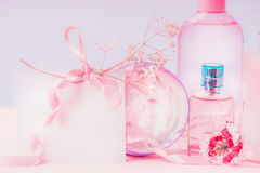 Empty greeting card laid and pink cosmetic products setting. Invitation, coupon, discount and sale. Beauty. Skin and hair care concept stock images