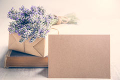 Empty greeting kraft card in front of a lavender bouquet, wrapped gift and old book over a white wood background. Vintage style. Stock Photo