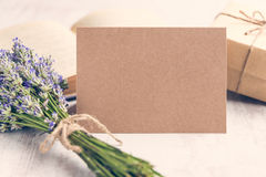 Empty greeting kraft card in front of a lavender bouquet, wrapped gift and old book over a white wood background. Vintage style. Stock Images