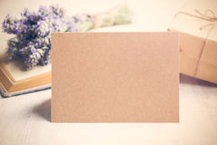 Empty greeting kraft card in front of a lavender bouquet, wrapped gift and old book over a white wood background. Vintage style. Royalty Free Stock Image