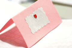 Empty greeting / wedding card with place for tex. Blank pink wedding / greeting card with a red heart and copy space for text Royalty Free Stock Images