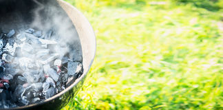 Empty Grill with coals and smoke on a background of grass, outdoor Royalty Free Stock Images