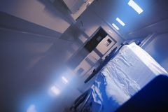 Empty gurney with a crumpled sheet in the long hospital hall stock image