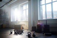 Empty Gym in Sunlight. Background image of gym equipment: kettlebells wooden boxes and tire stands in bright sunlight Royalty Free Stock Images