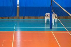 An empty gym with a volleyball net, chairs and display Board in the school.  stock photos