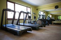 Modern gym interior with various equipment. Empty gym and workout equipment for legs, hands etc Stock Images