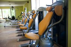 Modern gym interior with various equipment. Empty gym and workout equipment for legs, hands etc Stock Image