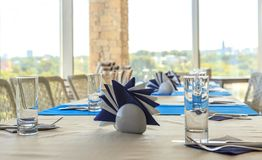 Empty half-served banquet table in restaurant with napkins, glasses, forks, knives, shallow DOF view against blurred city skyline Royalty Free Stock Images