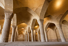 Empty hall of old Persian mosque Vakil with tall columns Stock Photos